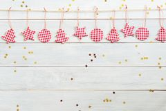 Christmas decorations hanging on wooden background with falling golden star Royalty Free Stock Images