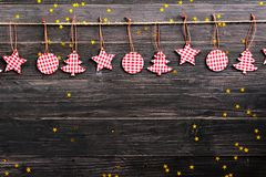 Christmas decorations hanging on wooden background with falling golden star Stock Photos