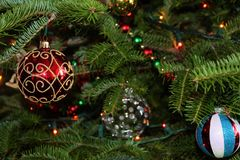 Christmas ornaments glowing on a green pine tree Royalty Free Stock Photos