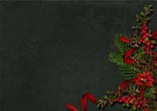 Christmas decorations with holly and poinsettia on a dark. Christmas decorations with fir branches, berries and on a dark background with space for photo and Stock Photos