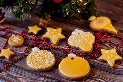 Christmas decorations. Honey cookies, glazed by yellow, white patterns laying near red beads, green pine tree branch on wooden tab Royalty Free Stock Image
