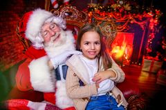 Christmas decorations and interior. A happy young girl is near Santa Claus at home. Merry Christmas and Happy New Year royalty free stock image