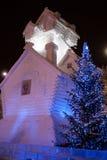 Christmas decorations: log snowy terem and lit Christmas tree lights. Royalty Free Stock Photos