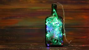 Christmas decorations. Luminous garland in a bottle on a wooden background stock footage