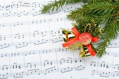 Christmas decorations lying on notes sheet Stock Image