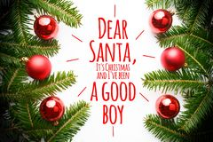 Christmas decorations with the message `Dear Santa, it`s Christmas and I`ve been a good boy`. Decoration made of fir branches and red Christmas ornaments with Royalty Free Stock Photography