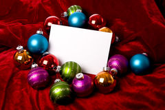 Christmas Decorations Notecard. A blank notecard surronded by Christmas decoration or baubles on a red background, add copy or graphic Royalty Free Stock Photos