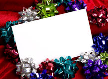 Christmas Decorations Notecard. A blank notecard surronded by Christmas decoration bows on a red background, add copy or graphic, Christmas party invitation Royalty Free Stock Image