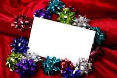 Christmas Decorations Notecard. A blank notecard surrounded by Christmas decoration bows on a red background, add copy or graphic, Christmas party invitation Royalty Free Stock Images