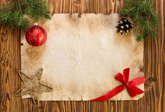 Christmas decorations on the old sheet of paper on a wooden back. Ground, place for text Royalty Free Stock Photo