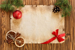 Christmas decorations on the old sheet of paper on a wooden back. Ground, place for text Stock Photo