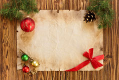 Christmas decorations on the old sheet of paper on a wooden back. Ground, place for text Stock Photos