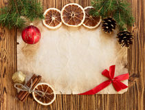 Christmas decorations on the old sheet of paper on a wooden back Royalty Free Stock Photography