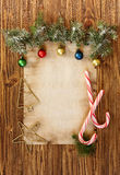 Christmas decorations on the old sheet of paper on a wooden back. Ground, place for text Stock Images