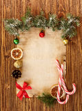 Christmas decorations on the old sheet of paper on a wooden back Royalty Free Stock Image