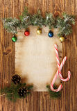 Christmas decorations on the old sheet of paper on a wooden back. Ground, place for text Royalty Free Stock Photos