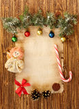 Christmas decorations on the old sheet of paper on a wooden back. Ground, place for text Stock Photography