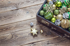 Christmas decorations in an old vintage suitcase on wooden board Stock Photography