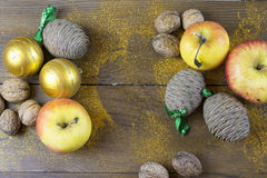 Christmas decorations on a old wood board. Christmas balls, apples and fir cone on a old wood board Royalty Free Stock Photo