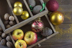 Christmas decorations on a old wood board. Christmas balls, apples and fir cone in old wooden box on a old wood board Stock Photography