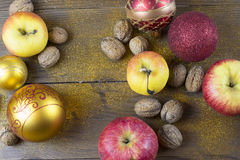 Christmas decorations on a old wood board. Christmas balls, apples and nutmeg on a old wood board Royalty Free Stock Images