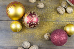 Christmas decorations on a old wood board. Christmas balls and nutmegs on a old wood board Royalty Free Stock Photos