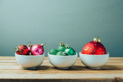 Christmas decorations and ornaments on wooden table. Three bowls with Christmas balls. Retro filter effect Stock Images