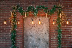 Christmas decorations over the decorative fireplace on the wall. Christmas decorations over the decorative fireplace, hanging toys, decorations and light bulbs stock images