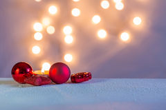 Christmas decorations in pastel and red. Lights come out from red christmas decorations with candle on snow on pastel colors Royalty Free Stock Photos