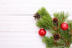 Christmas decorations on a pine branch on a white wooden backgro Stock Images