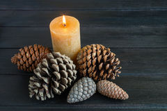 Christmas decorations. With pine cones and burning candle on black wood Royalty Free Stock Image