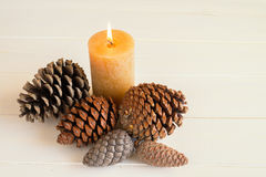 Christmas decorations. With pine cones and burning candle on white wood Stock Photos