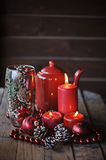 Christmas decorations and pine cones in glass vase. With red candles and tea pot on the background Stock Photos