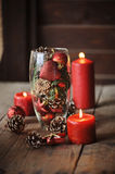 Christmas decorations and pine cones in glass vase Stock Image