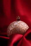 Christmas decorations on red. Christmas decorations on a red silky background Royalty Free Stock Images