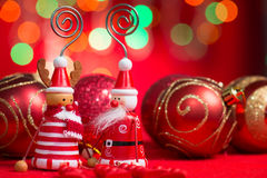 Christmas decorations on red background. Christmas ornaments santa claus and reindeer with blurry glitter shiny lights at background Royalty Free Stock Photography
