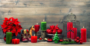 Christmas decorations with red candles, flower poinsettia, stars. And baubles. vintage style toned picture Royalty Free Stock Image