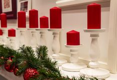 Christmas decorations and red candles stand on the fireplace royalty free stock images