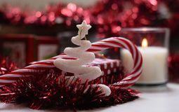Christmas decorations, red color, lit candle, front view. Blurred background Stock Image