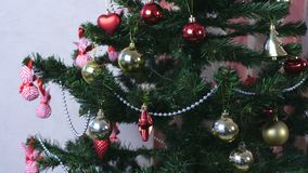 Christmas decorations in red and gold and silver beads on the branches of the Christmas tree. Christmas decorations in red and gold and silver beads on the stock footage