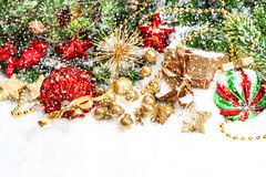 Christmas decorations in red, green, gold alling snow effect. Festive christmas decorations in red, green, gold. Shiny baubles and gift box with christmas tree Stock Images
