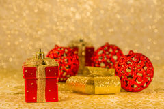 Christmas decorations. Red Christmas ornaments, golden ribbon and Christmas decoration on golden background Royalty Free Stock Photo