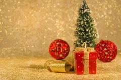Christmas decorations. Red Christmas ornaments, golden ribbon and snowed Christmas tree on golden background Stock Photos