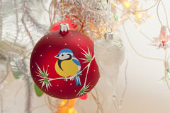 Christmas decorations. Red christmas toy with bullfinches in the form of a ball hanging on a branch Royalty Free Stock Photography
