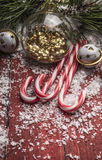 Christmas decorations on a red wooden background with pine branches and candy cane close up Royalty Free Stock Images