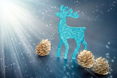 Christmas decorations: reindeer figure and cones. Christmas decorations: reindeer figure and golden cones with snowflakes in light rays background, closeup shot Royalty Free Stock Images