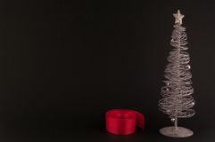Christmas decorations. Ribbon for wrapping Gifts and silver Christmas tree on black background stock images