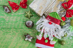Christmas decorations, Santa Claus and chocolate. Old green wooden background, place for inscription. Royalty Free Stock Photos