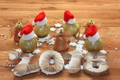 Christmas decorations, Santa`s hats on balls, the new year 2018, wooden background. And snowflakes Royalty Free Stock Photos