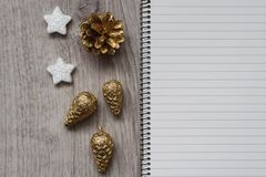 Christmas decorations, Santa`s white boot, golden fir cones, snowflakes and an open blank notebook, wooden background stock photo
